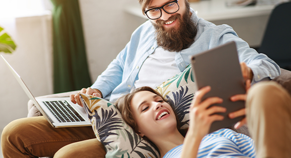 Couple looking at computer on the couch